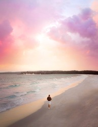Drone photo with vibrant colourful sky with man standing on long beach in Jervis Bay on the south coast of New South Wales