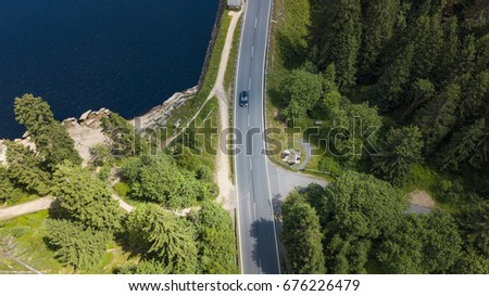 Drone photography with a street crossing the harz national park at the edge of a mountain lake surrounded by fir trees. #676226479