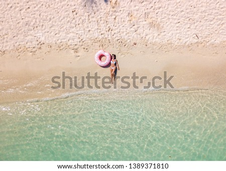 Drone pictures aerial view of a girl on the beach with crystal clear water, a floating boat and boats on a sunny day