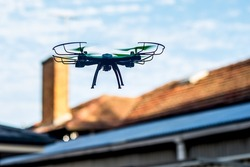 Drone quad copter flying over the roofs. Drone photography and videography. Toy drone flight. Copy space
