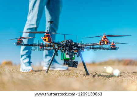 Drone quad copter ready to start flying. Cropped image of man legs standing near drone with digital camera. Clear blue sky on the background. Active timespending concept.