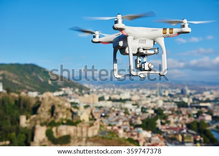 Shutterstock drone quad copter with high resolution digital camera flying hovering in the blue sky over the city