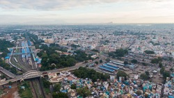 drone shot aerial view Madurai tamilnadu india apartments houses cityscape crowded busy place huge mega city metropolitan railway track station roads traffic sky clouds construction