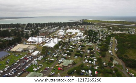 Drone shot of folk music festival with pretty river in foreground. #1217265268