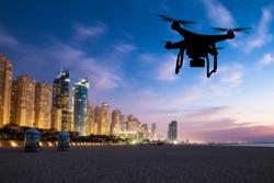 Drone silhouette flying above Dubai city panorama
