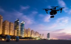 Drone silhouette flying above Dubaicity panorama