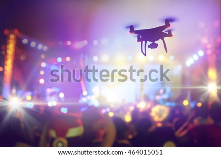 Drone silhouette flying above live concert, Taking photo of concert stage, music festival, happy youth, luxury party, landscape exterior. facebook live. shooting photo and video with drone flying.