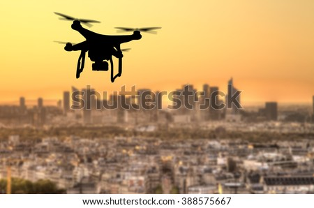 Drone silhouette flying above Paris city panorama