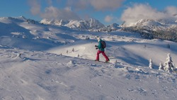 DRONE: Spectacular shot of a snowy valley as young woman hikes along a meadow during a ski touring trip in Velika Planina. Fit female splitboarder hikes up a scenic mountain in picturesque Slovenia.