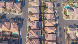 DRONE, TOP DOWN: Flying row houses in a luxury suburban neighborhood in Nevada. Cinematic shot of terraced houses and backyards in the sunny suburbs of Las Vegas. Empty streets of American suburbia.