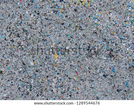DRONE, TOP DOWN: Flying towards a huge stinky piles of scrap and plastic piling up in a big junkyard. Harmful waste an trash being collected in an industrial landfill. Large garbage disposal site.