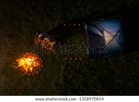 DRONE, TOP DOWN: Joyful couple camping in the wild roasting sausages over the large campfire. Flying above young man and woman making a midnight snack during a camping journey in the serene nature.