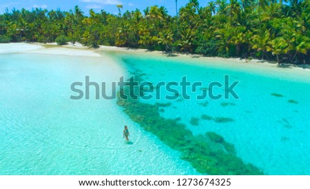 DRONE: Tourist girl in blue bikini walks into the shallow turquoise ocean water surrounding the small tropical island in the middle of the Pacific. Caucasian woman strolling around white sand beach.
