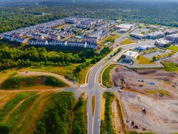 Drone view of a city residential area in the foreground is a construction site with construction equipment.