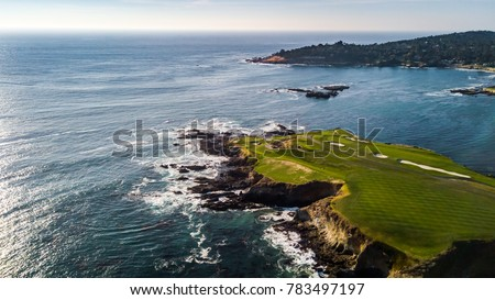 Drone view of a golf course next to the ocean with waves hitting the rocks on the seashore #783497197