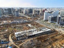 Drone view of a large construction site. Tower cranes in action on fog background. Housing renovation concept. Crane during formworks. Construction the buildings and multi-storey residential homes