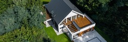 Drone view of modern and elegant house exterior in green forest, panorama