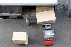 Drone view of movers at work unload new furniture and boxes from moving truck. Situation with moving house worker, manually download the furniture from a back of a truck. View from above.