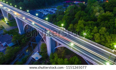 Drone view of the illuminated Matsesta viaduct and mountainside with dense forest at twilight, Sochi, Russia #1151265077