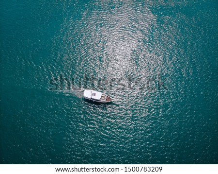 Drone view of the light boat in the turquoise sea, leaving a beautiful trace on the water; relaxation and peace; tranquility concept. #1500783209