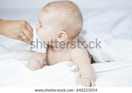 Drooling sick baby with a cold and running nose getting wiped by mom's hand, lying naked in white sheets