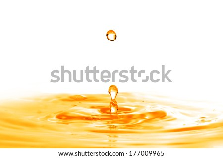 drop falling into orange water with splash isolated on white