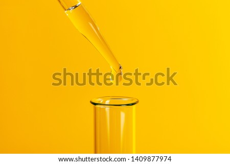 Drop the pipette into the test tube. The study of biological material. Laboratory research. Yellow background #1409877974