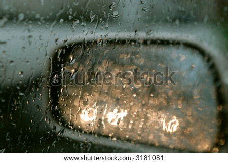 Droplets and car lights reflections through foggy car window and rear view mirror