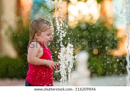 Droplets of water are going every place as this child is playing on a hot summer day.