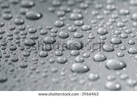 Droplets on a car. Short depth of field. The image may appear grainy, but it\'s caused by the metallic paint.