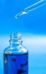 Dropper glass Bottle Mock-Up. Oily drop falls from cosmetic pipette on blue background. Color of the year, close up dropper with Cannabis CBD Oil used for medical purposes.marijuana CBD oil on blue