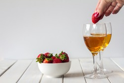 Dropping Strawberry in Wine in Glasses and a Bowl of Strawberries on a White Wooden Table with Copy Space