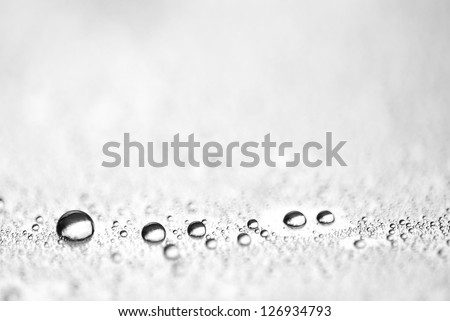 Drops in row on metal surface with shallow depth of field