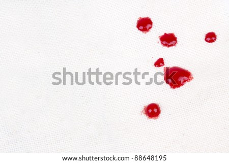 Drops of blood on a piece of cloth.
