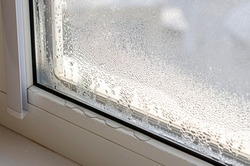 Drops of condensate and black mold on a substandard metal-plastic window. Plastic. Ecology