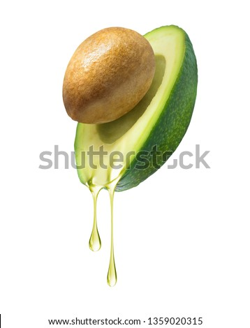 Drops of oil dripping from avocado on a white background