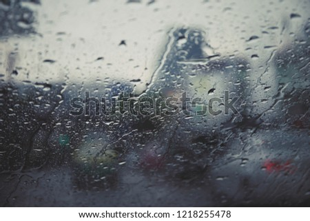 Drops Of Rain Drizzle on the glass windshield in the evening. street in the heavy rain. Bokeh Tail light. soft Focus. Please drive carefully, slippery road. soft focus.