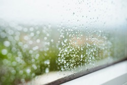 Drops of rain horizontal background. Winter seasonal time. Humidity and rainy weather inside home. Water condensation on window. Detail of wet drops of rain stick to a clean window at home.