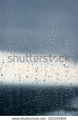 Drops of rain on a window glass.Through the window view of the sea and overcast clouds #326184806