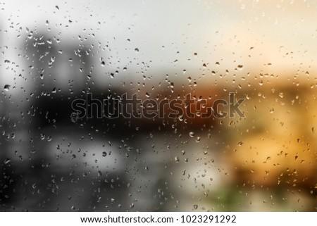 Drops of rain on a window pane, street buildings in background. #1023291292