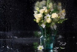 Drops of rain on a window pane with beautiful defocused white bouquet of asters, roses and alstroemerias as background. Painting effect. Copy space. Amazing postcard.