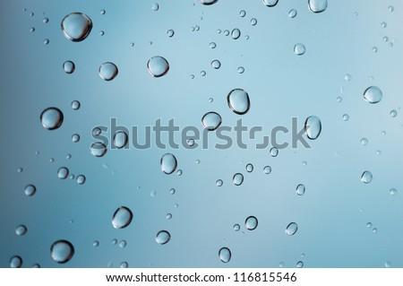 Drops of rain on blue glass