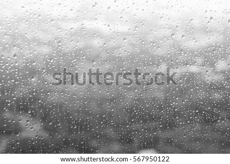 Drops of rain on blue glass background / drops on glass after rain #567950122