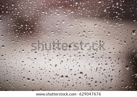 Drops of rain on the glass, many small droplets. Behind beige background, street. #629047676