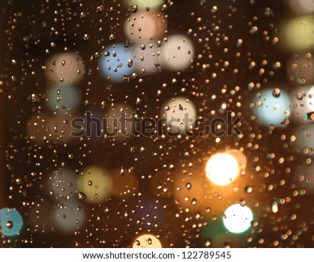 Drops of rain on window, night. On back plan washed away lights of the torches. Shallow DOF