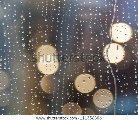Drops of rain on window with abstract lights