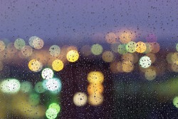 Drops of rain on window with bokeh lights background