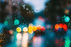 Drops Of Rain Water In Night Or Evening Street Lights On Blue Glass Background. Street  Bokeh Boke Lights Out Of Focus. Autumn Abstract Backdrop