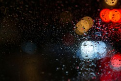Drops of Rain Water In Night or Evening Street Lights on car Glass Background. Street Bokeh Lights Out of Focus. Water drop on window. Out of focus, Bokeh light. Tailights and traffic in bokeh light.