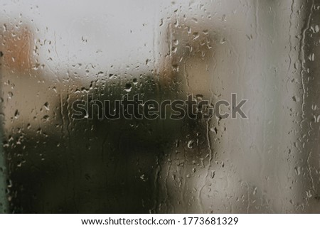 drops of rain water on the glass. drops collected on the window against the background of multi-storey buildings.